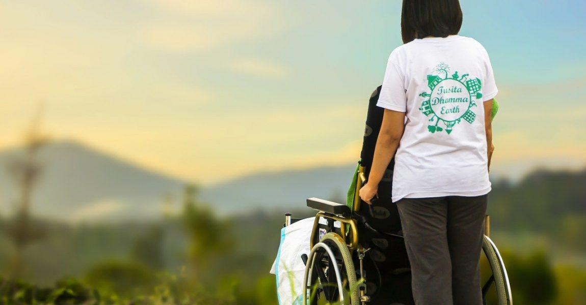 Pflegerin mit Rollstuhlpatient